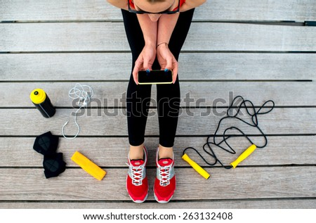 Sporty woman holding phone with empty screen sitting on the sunbed with jump rope, gloves and drink bottle on background  - stock photo