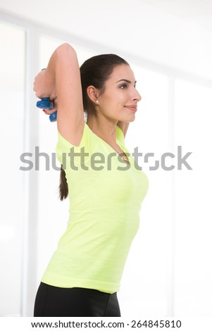 Sporty woman in yellow t-shirt hold dumbbells behind her back - stock photo