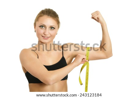 Sporty woman is measuring her biceps - stock photo