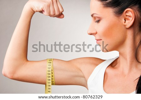 sporty woman is measuring her biceps on grey background - stock photo