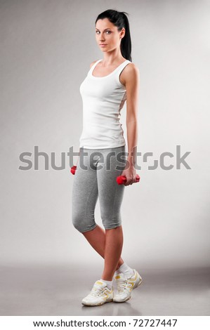 sporty woman is standing with barbells on grey background - stock photo