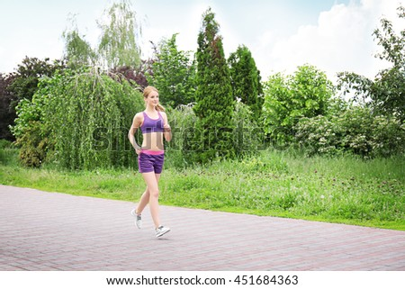 Sporty woman jogging at park on a sunny day