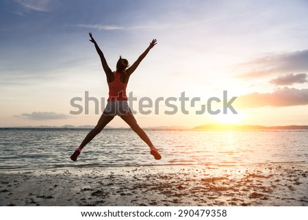 Sporty woman jumping and enjoying freedom and success towards the sun and sea on sunset at the beach.
