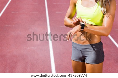Sporty woman looking her watch against race track