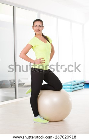 Sporty woman posing for camera with  pilates ball  - stock photo