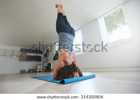 Sporty woman practice yoga, doing supported headstand yoga asana. Rear view of fitness female practicing Salamba Sirsasana pose at gym. - stock photo
