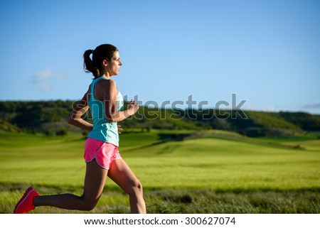 Sporty woman running. Female athlete training outdoor against countryside green field. - stock photo