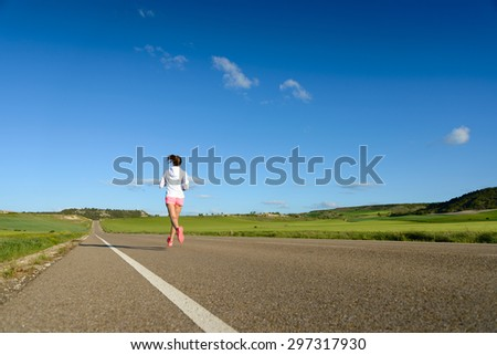 Sporty woman running on country side road back view. Female athlete training outdoor. - stock photo
