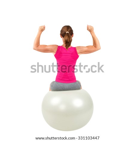 Sporty woman sitting on a gymnastic-ball and doing workout - isolated