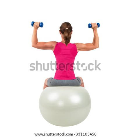 Sporty woman sitting on a gymnastic-ball and doing workout - isolated - stock photo