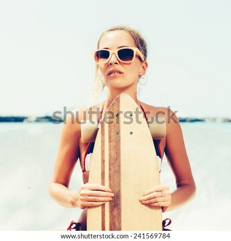 Sporty woman skateboarder in sunglasses with a longboard. Outdoor lifestyle portrait of girl