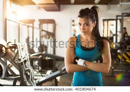 Sporty woman standing with arms crossed in fitness gym. - stock photo