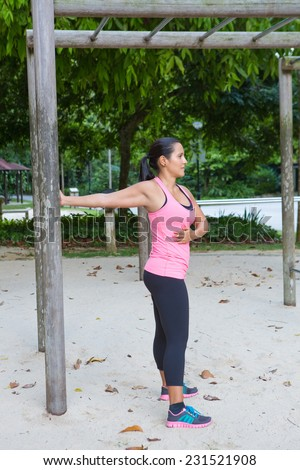 Sporty woman stretching upper arm by wooden post in exercise park - stock photo