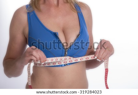 Sporty woman wearing a sports bra checking bust size with a tape measure