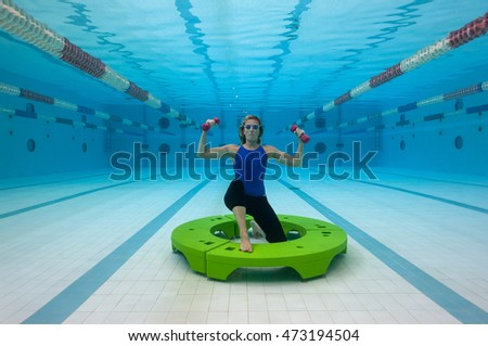 Sporty woman wearing blue swimsuit practicing aquagym inside swimming pool.