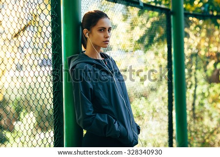sporty woman wearing  jacket and listening music outdoors in the park, standing near mesh fence