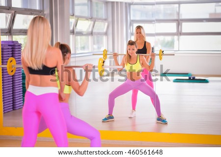 Sporty woman with barbell doing squats, instructor monitors the process