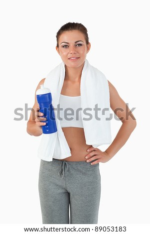 Sporty woman with bottle against a white background