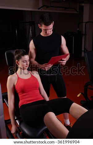 sporty woman with trainer exercise weights lifting in fitness gym - stock photo