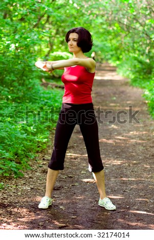 sporty woman working out on a forest path.