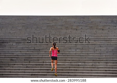 sporty woman working out running up stairs outdoors for morning workout - stock photo