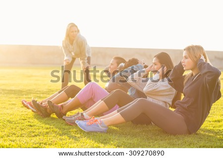 Sporty women doing sit ups during fitness class in parkland - stock photo
