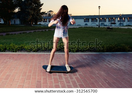 Sporty women is riding skateboard in city park. Yong girl on skate with both feet on. Extreme riding activity. Urban sport. Retro color warm toned image. Dynamic shot. - stock photo