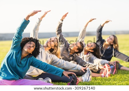 Sporty women stretching during fitness class in parkland - stock photo