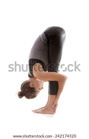 Sporty yoga girl on white background exercises, head to knees pose - stock photo