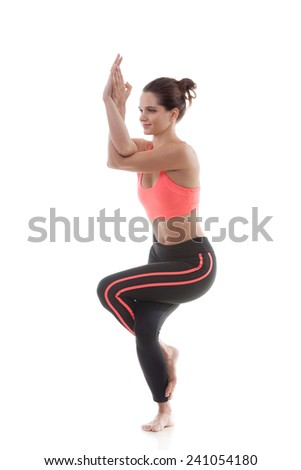 Sporty yoga girl on white background in garudasana (Eagle Pose) - stock photo