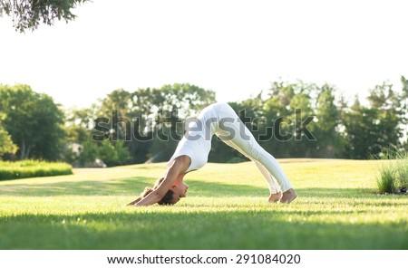 Sporty yogi girl stretching in pose Adho Mukha Svanasana. Girl in white sports suit training in the air. - stock photo