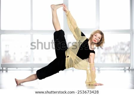 Sporty yogi woman doing exercises, full version of Side Plank Yoga Pose, Vasisthasana, top leg perpendicular to the floor in class - stock photo
