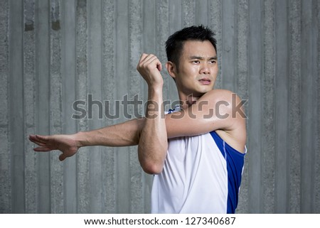 Sporty Young Asian man stretching outdoors in urban city. Male fitness concept.