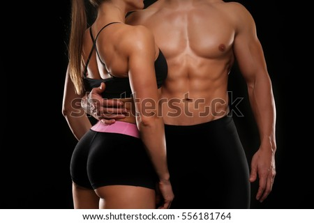 Sporty young couple on black background, closeup