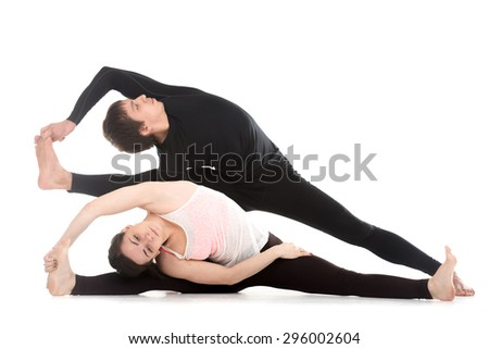 Sporty young couple on white background doing different side bend exercises, yoga, fitness or pilates practice with partner, studio shot, full length - stock photo