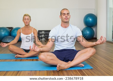 Sporty young couple sitting in lotus posture with eyes closed at fitness studio