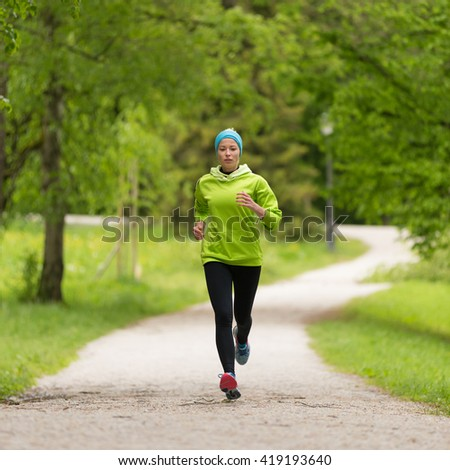 Sporty young female runner in city park.  Running woman. Female runner during outdoor workout in nature. Fitness model outdoors. Weight Loss. Healthy lifestyle.  - stock photo