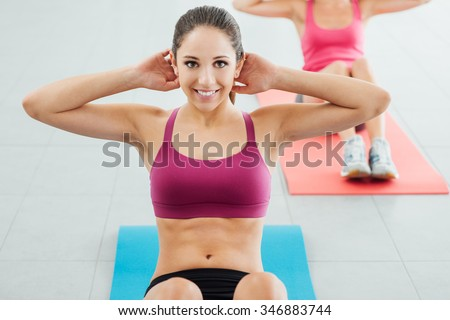 Sporty young girl at the gym doing abdominals workout on a mat, she is smiling at camera, fitness and health concept - stock photo