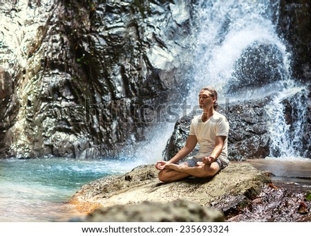 sporty young man practicing yoga near a waterfall in the mountains - stock photo