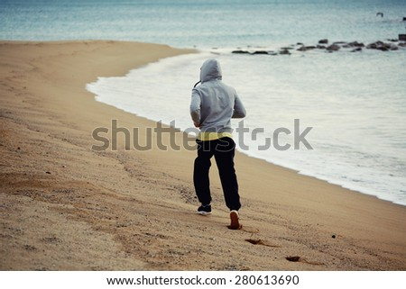 Sporty young man working out at early morning while run along the seashore over wet sand, male jogger exercising on the beach while jogging near sea waves, runner working out outdoors - stock photo