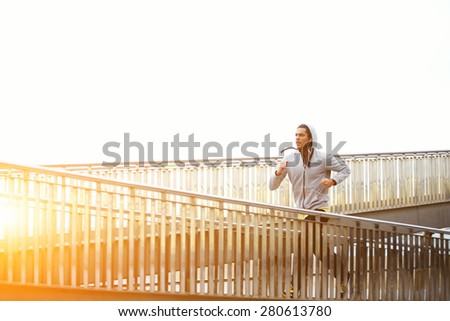 Sporty young man working out at early morning while run up the bridge with orange sunrise on background, male jogger exercising while listening to music with headphones, runner working out outdoors - stock photo