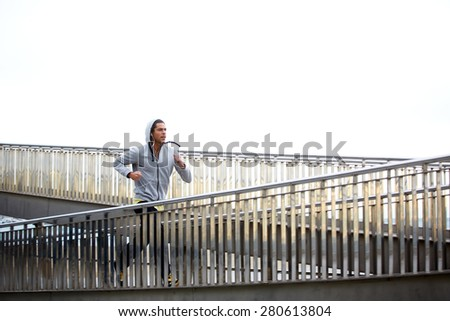 Sporty young man working out at early morning while run up the bridge with overcast sky on background, male jogger exercising while listening to music with headphones, runner working out outdoors - stock photo