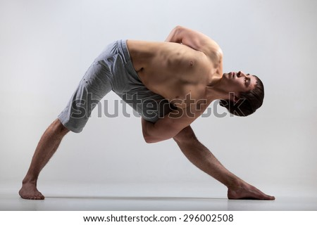 Sporty young man working out, yoga, pilates, fitness training, doing Utthita Trikonasana, Extended Triangle pose with hands behind back, studio shot, full length - stock photo