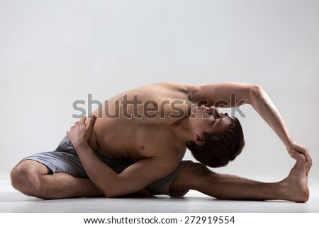Sporty young man working out, yoga, pilates, fitness training, sitting in Revolved Head to Knee pose, Parivrtta Janu Sirsasana, yoga for relieving stress - stock photo