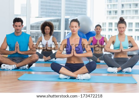 Sporty young people in Namaste position with eyes closed at a bright fitness studio