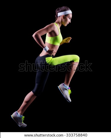 Sporty young running girl on black - stock photo
