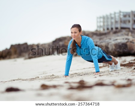 Sporty young woman doing push ups on the sea coast - stock photo
