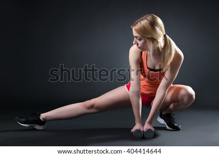 sporty young woman doing stretching exercise with two dumbbell on the floor and looking her shoes - stock photo