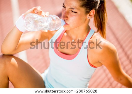 Sporty young woman drinking water - stock photo