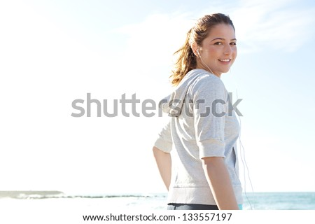 Sporty young woman on a beach taking a break from exercising and listening to music with her head phones, turning and smiling at camera against a blue sky.